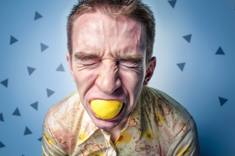 man-with-eyes-closed-and-lemon-in-mouth
