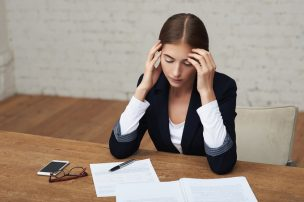 Overworking business woman suffering from headache sitting at office and reading documents