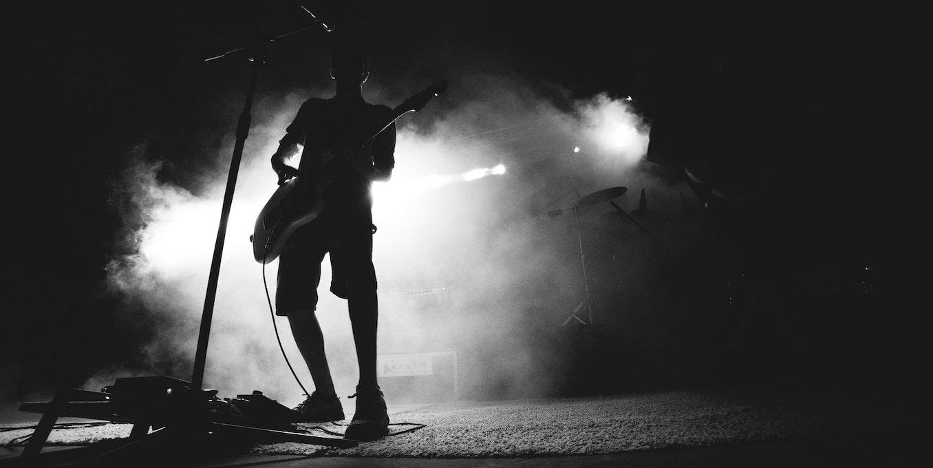 イカ天について説明した記事中のイメージ画像。モノクロ画像で、舞台でギターを演奏する人物に背後から淡いライトが当たっている。