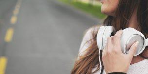 「メンタルを強くする音楽とは」という記事中のイメージ画像です。路上で女性が白いヘヘッドホンを首にかけて音楽の余韻にひたっています。