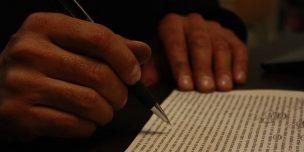 作詞コンテストについて書かれた記事中のイメージ画像です。びっしりと書かれた文字の上にペンが止まります。