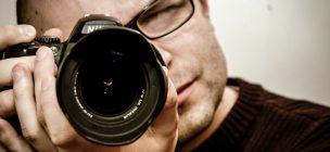 おすすめの宣材写真でオーディションの合格を勝ち取ろう、という記事中のイメージ画像です。カメラマンがファインダーをのぞきカメラのレンズをこちらへ向けています。