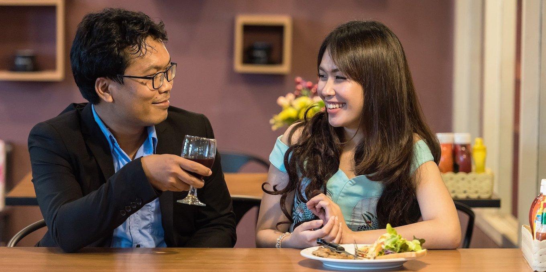 上手な話し方の基本について記された記事中のイメージ画像です。カウンターでワイングラスを傾ける男性が隣の女性に微笑みかけています。