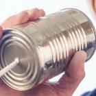 滑舌を改善する原因と方法について解説した文章のイメージ画像です。糸電話に向かって笑顔で話しかける人物が写っています。
