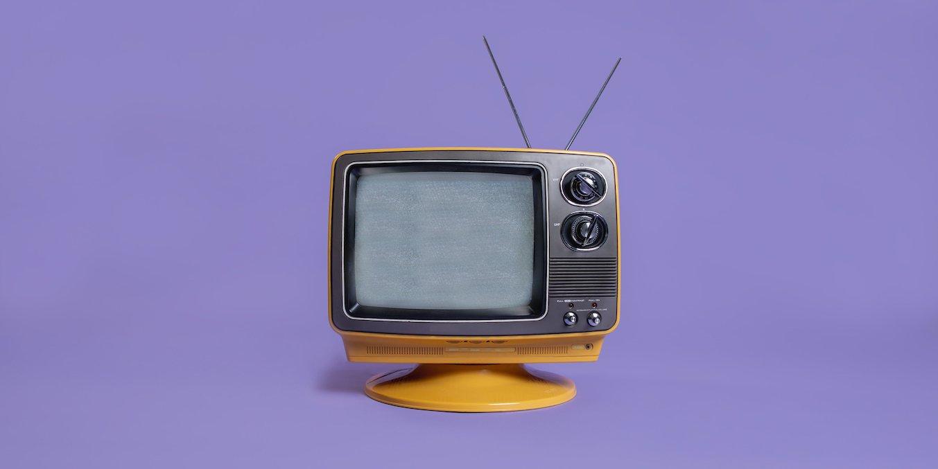 「赤ちゃんにテレビ いつからどれくらい見せていいのかを確認」という記事のイメージ画像です。紫の背景に古くて小さなテレビが一台写っています。