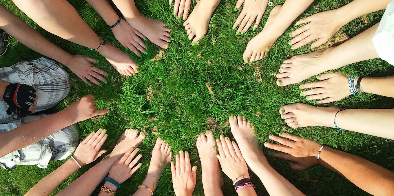 「ラストアイドルとは」という記事中のイメージ画像です。芝生の上に輪を描くように、たくさんの女性が手や足を差し出しています。