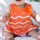 「赤ちゃんの服、買いすぎには注意!生後半年までの上手な選び方」という記事中のイメージ画像です。おしゃれなワンピースを着た赤ちゃんが座ってこちらを見て笑っています。
