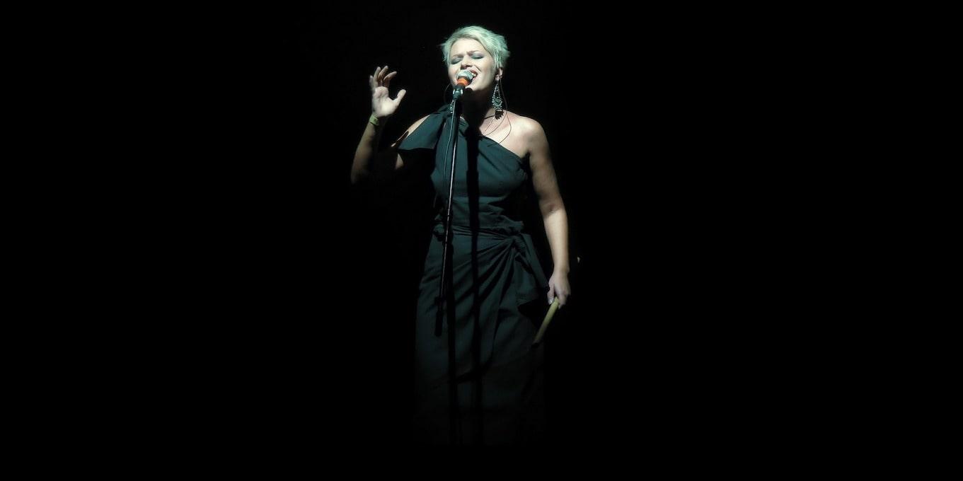 オランダ初のオーディション番組、ザ・ヴォイスについて解説した記事中のイメージ画像です。まっくらなステージ上でマイクの前にたった女性歌手にスポットライトが当たります。