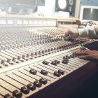 「ラジオパーソナリティーになるには?方法や必要なスキルを紹介」という記事中のイメージ画像です。音量を調節するたくさんのツマミがならんでいます。