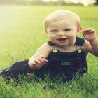 「赤ちゃんモデルのスキンケア」という記事中のイメージ画像です。赤ちゃんがオーバーオールを着てこちらに微笑んでいます。