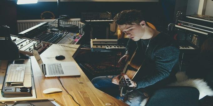 「楽曲を提供したい【悠々自適の印税生活】どうすればなれる?何が必要?」という記事のイメージ画像です。男性がギターとPCに向かって作曲をしています。